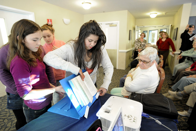 Moore Middle School students from Portland visit residents at the Inn at Village Square in Gorham on Monday to present the residents with adaptive devices for reading and drinking. Julia Martin and Andrea Castro show resident Alice Nicol a book holder.