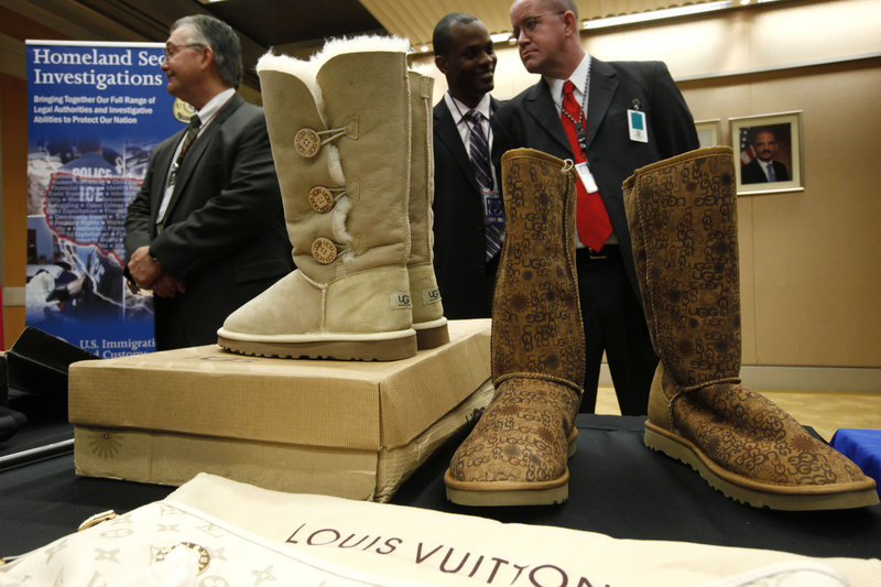 Fake Ugg brand boots are displayed at the Justice Department in Washington during Monday's news conference with Attorney General Eric Holder about seizures of websites involved in the illegal sale of counterfeit goods and copyrighted works.