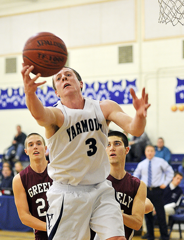 Josh Britten of Yarmouth, who led all scorers with 21 points, reaches for a rebound in front of Caleb King, left, and Jake Levite during the first half of Greely's 61-53 win Monday at Yarmouth.