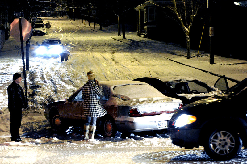"""A Portland police officer, left, stands by one of two motorists who collided after sliding down Walnut Street to Washington Avenue on Monday. Other drivers, in background, used the curb to stop during Greater Portland's first snowstorm of the winter, which created major traffic problems for evening commuters. Hundreds of vehicles slid off the slick roads. """"It was a horror show,"""" said Portland police Lt. Gary Hutcheson."""