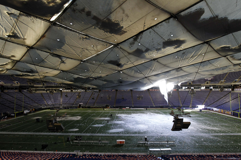 Snow falls into the field from a hole in the collapsed roof of the Metrodome in Minneapolis today. The inflatable roof of the Metrodome collapsed today after a snowstorm that dumped 17 inches Minneapolis. No one was hurt.