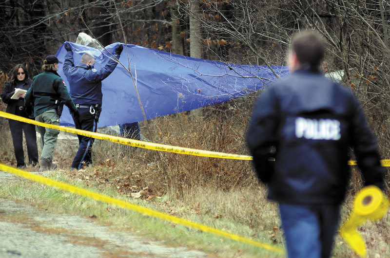 Police cover human remains discovered Sunday morning by Game Wardens off Outer Winthrop Street in Hallowell. Wardens, searching with dogs, located the body just after noon near the granite quarries.