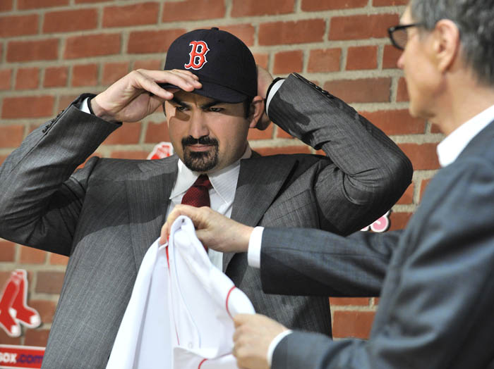 New Boston Red Sox first baseman Adrian Gonzalez pulls on his team cap as team owner John Henry holds out his new jersey during a news conference today at Fenway Park.