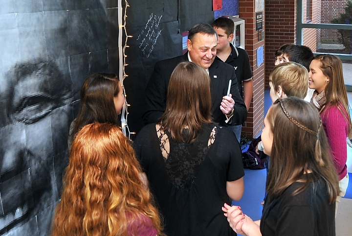 Gov.-elect Paul LePage visits Lyman Moore Middle School in Portland and talks with students after signing the wall next to a large photo of himself.