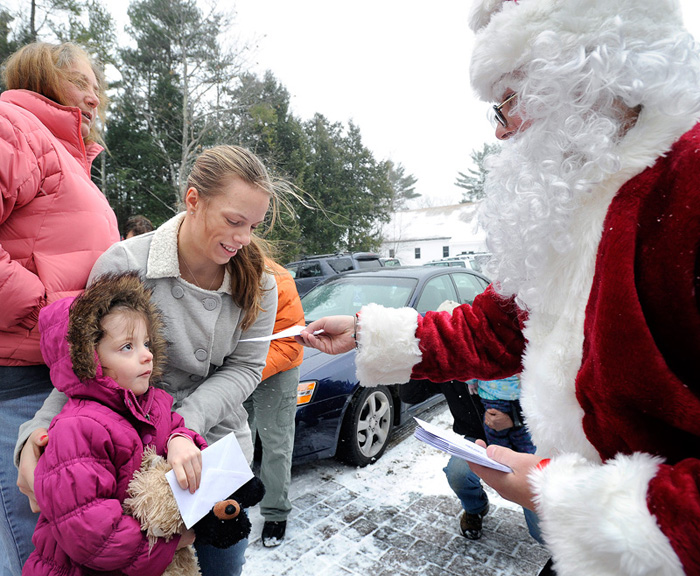 The Secret Santa paid a visit to The Warming Hut in Sebago to give away $100 bills during his first statewide visit today. He is seen here handing out two envelopes to 4-year-old Elana Labrecque and her mother Erica Labrecque.
