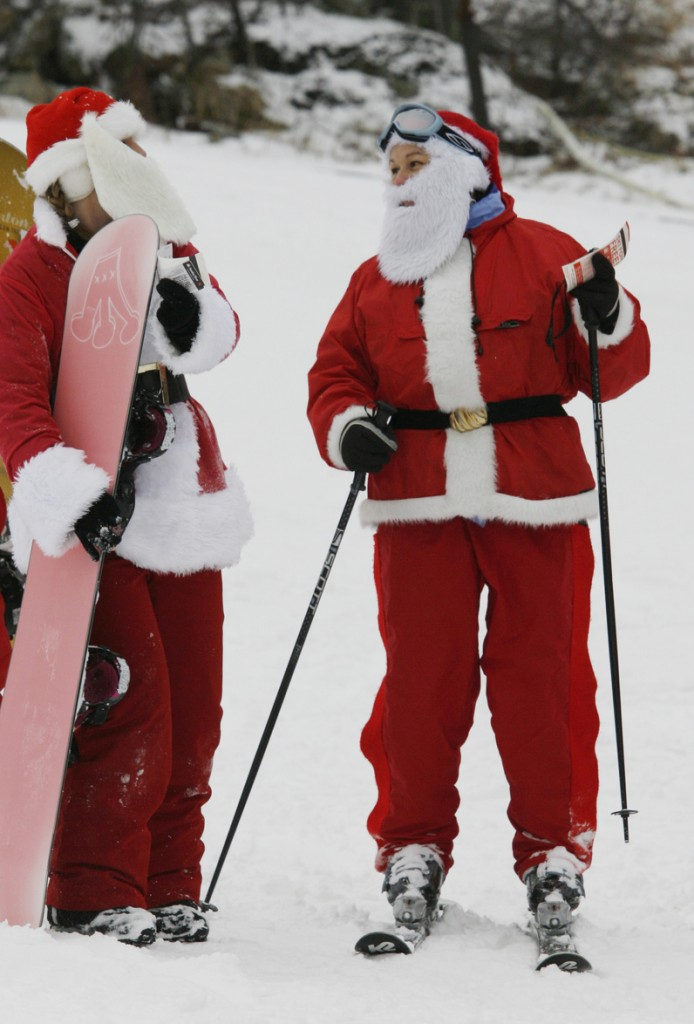 Lynn Philippone, right, speaks with Amy Bloodgood, left, Sunday during the 11th annual Santa Sunday at Sunday River in Newry, Maine. Participants get a free lift ticket if they dress as Santa and donate $10 or more to the Bethel Rotary Club's annual toy drive.