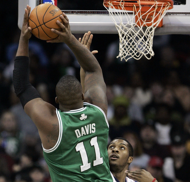 Glen Davis of the Celts takes a jump shot as New Jersey's Derrick Favors defends in the first half today at Prudential Center in Newark , N.J. The Celts won, 100-75.