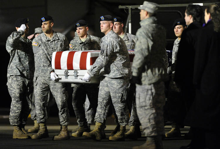 An Army carry team carries a transfer case containing the remains of Pvt. Buddy W. McLain at Dover Air Force Base, Del., on Wednesday.
