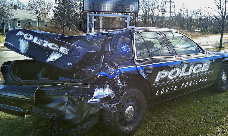 A police cruiser that was rear-ended on the Casco Bay Bridge sits on the South Portland side of the bridge as a warning against people using cell phones while driving.