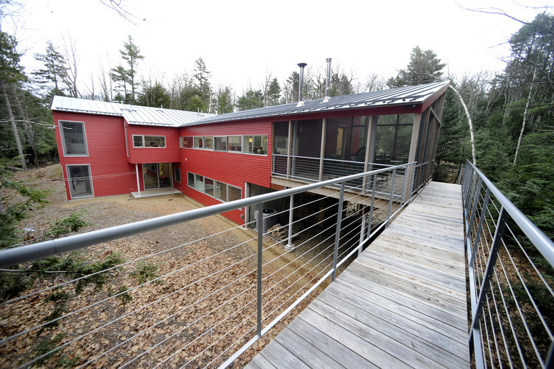 An exterior shot of the Weir home, with its elevated walkway off a large screened-in porch.