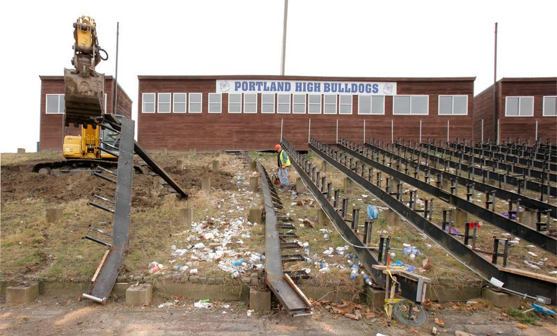 Workers from the city's public services department remove bleachers Tuesday at Fitzpatrick Stadium. Heavy equipment is used to take out large sections of seating.