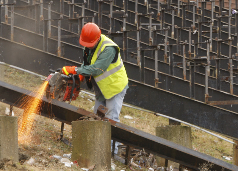 City worker Joe Meyers cuts a bleacher support.