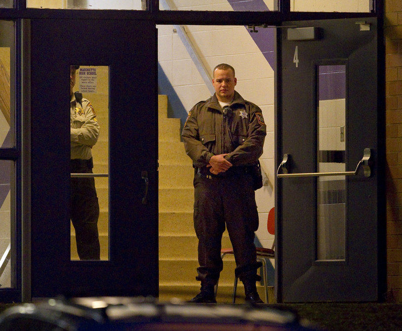Law enforcement officials stand guard in the doorway of Marinette High School Tuesday morning. School officials say they plan to review safety guidelines at the school, which does not have metal detectors.
