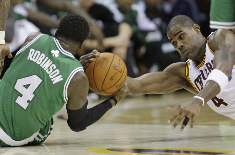 Boston's Nate Robinson and Cleveland's Antwan Jamison fight for the ball in the fourth quarter Tuesday night. The Celtics held the Cavs to 39 percent shooting.
