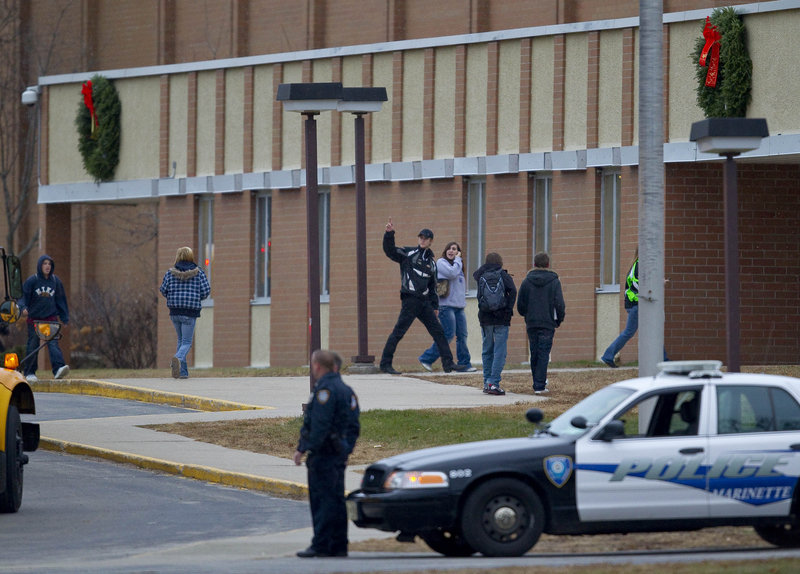 Students arrive for class at Wisconsin's Marinette High School as police stand guard outside Wednesday.