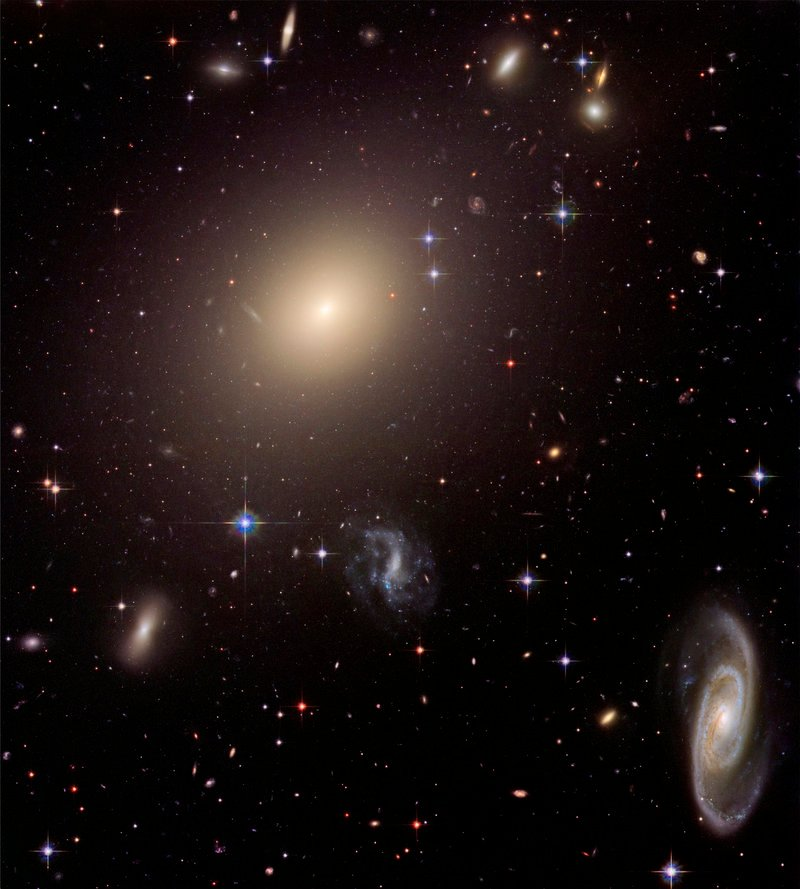 This photo provided by NASA, taken in 2006 by the Hubble Space Telescope, shows a cluster of diverse galaxies. A new study led by a Yale University astronomer looked at elliptical galaxies, such as the bright one in the top middle, and found they have far more stars than initially thought.