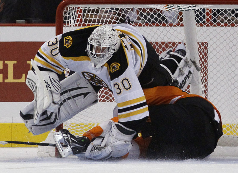 Bruins goalie Tim Thomas keeps the puck and the Flyers' Scott Hartnell out of the net in the first period Wednesday night in Philadelphia. Thomas later stopped Hartnell's penalty shot and made 41 saves in all for Boston.