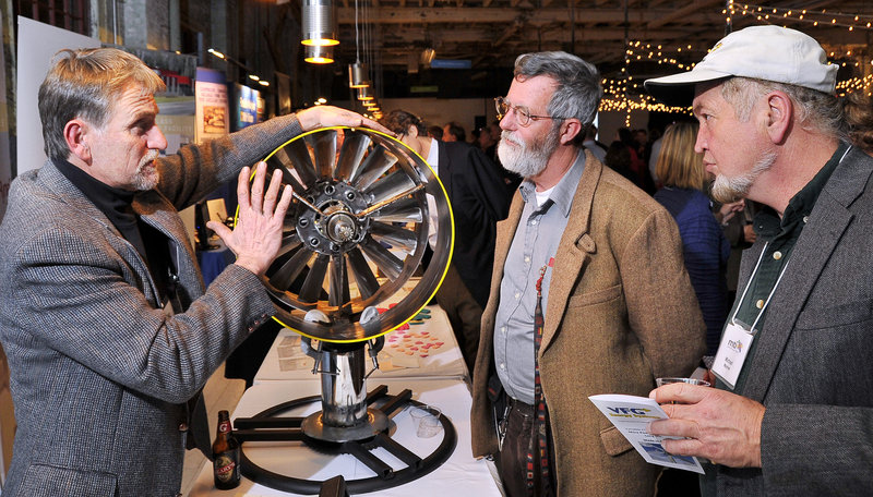 Benjamin Brickett, left, of VFG Energy Systems in Kittery demonstrates a prototype water turbine to Phineas Sprague Jr., center, and Michael Mayhew, a renewable energy consultant, during an event in Portland on Wednesday honoring Maine Technology Institute. Located in Gardiner, MTI was celebrating 10 years of recognizing companies that invest in and market Maine's innovation economy.