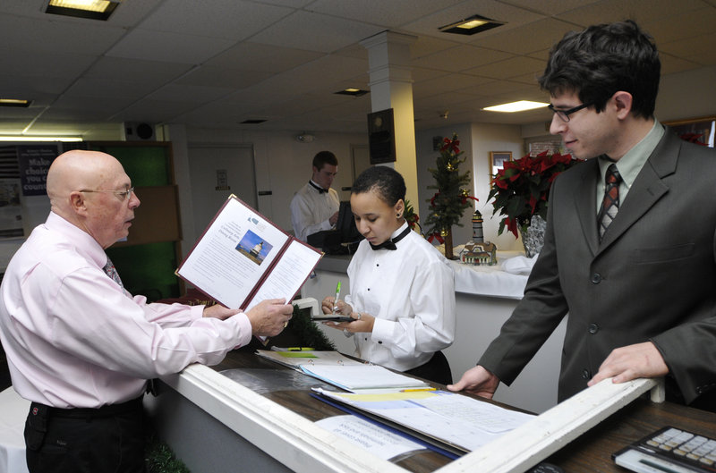 Chef Wilfred Beriau looks over the menu with Rosa Libby of Mount Vernon and maitre d' Noah Cohen of Scarborough as part of the dining room management program at Southern Maine Community College.