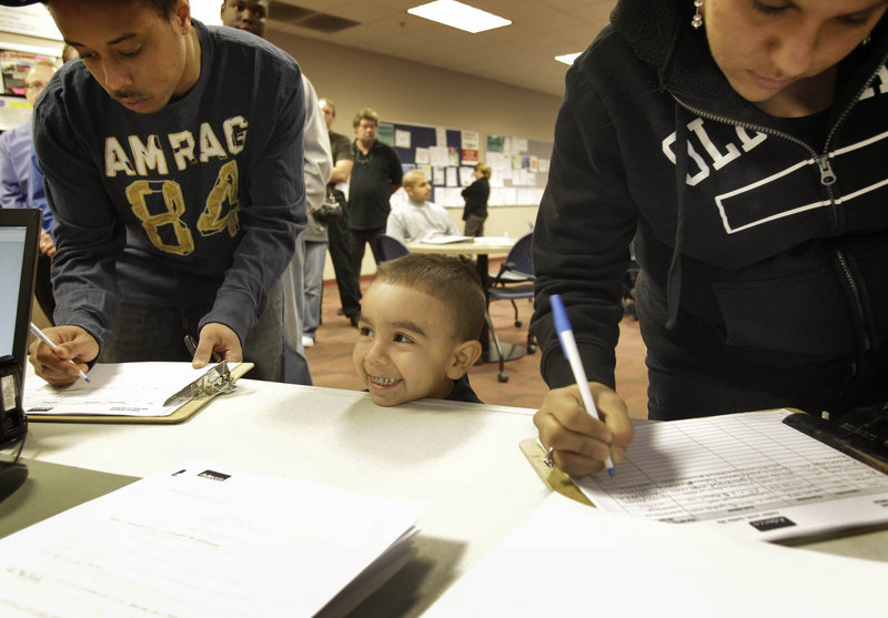 Diego Valdez, 3, waits for his mom, Veronica Majia, right, to sign in at a job fair in Phoenix, Ariz. More Americans applied for unemployment benefits last week, but the broader trend in layoffs points to a slowly healing jobs market.