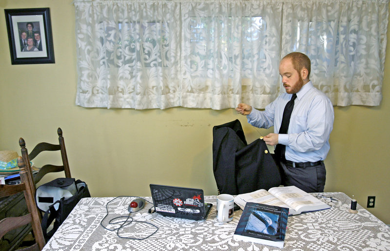 Geoffrey Voss, 27, sews a button on his jacket before leaving for a job interview in Prairie Village, Mo. The graduate of the University of Missouri-Kansas City has found the sluggish economy an obstacle in landing a job. Such job seekers with better educations are getting many jobs typically held by those with less education.