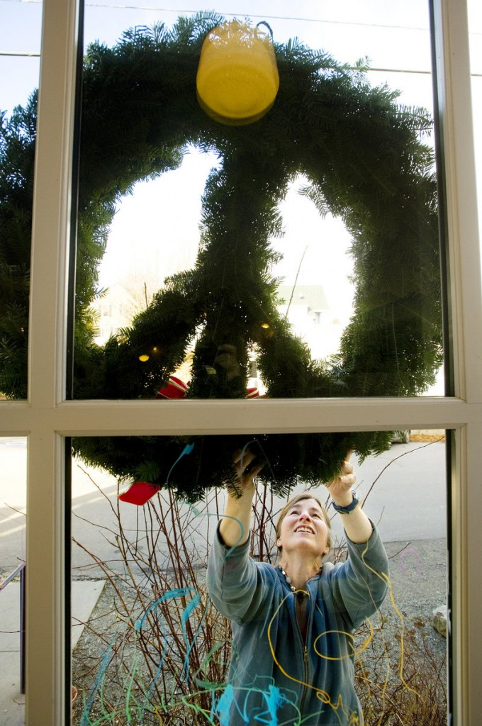 Christie Hallowell, executive director of North Haven Arts & Enrichment, hangs a Christmas wreath at Waterman's Community Center.