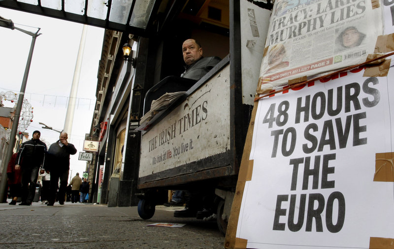 A man sells newspapers that reflect Europe's economic angst in Dublin, Ireland, last month. The debt crisis has forced eurozone governments to rewrite some of the currency union's most fundamental rules.