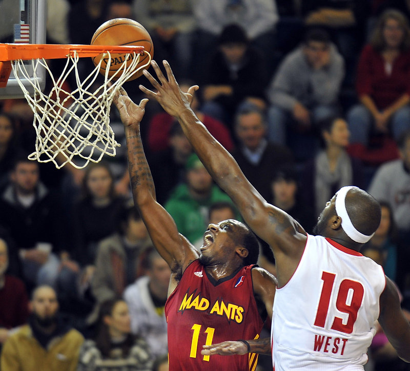 Fort Wayne's Walker Russell Jr. goes up for a layup in the first quarter Friday night, but Mario West blocks it to the delight of another sold-out crowd at the Portland Expo. West led the Red Claws with 19 points.