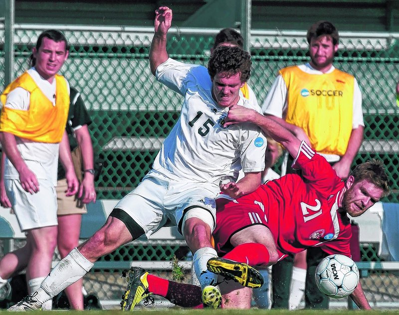 Tim Prior, left, of Bowdoin and Lynchburg's Benjamin Phelps get tangled up while trying to control a loose ball Friday in an NCAA Division III men's soccer semifinal at San Antonio. Lynchburg ended the Polar Bears' season with a 2-1 victory in overtime.