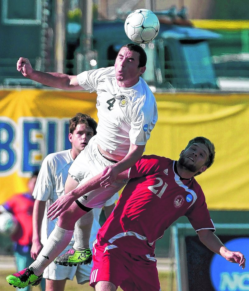 Bowdoin's Sean Bishop soars above Benjamin Phelps of Lynchburg and heads the ball. The Polar Bears led on a goal by Cape Elizabeth's Ben Brewster until the Hornets forced overtime with a goal in the 88th minute.