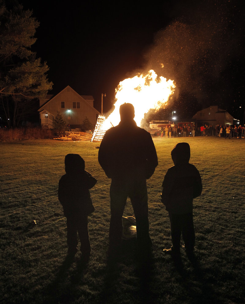 Sean Jenks of Kennebunk watches a bonfire with his sons Colby, 8, left, and Cian, 6, behind the Washington Hose Company in Kennebunk on Friday during Christmas Prelude.