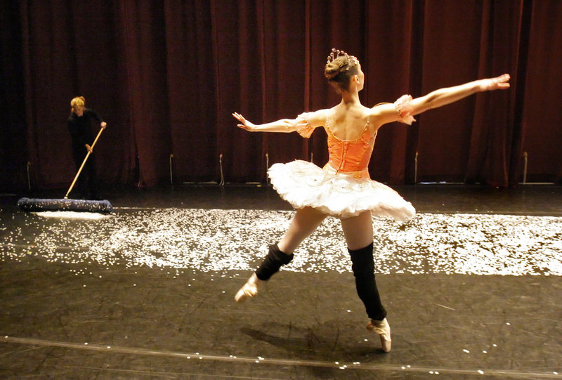 Kate Hamilton warms up on the stage during intermission while Lynn Gilbreath sweeps up confetti from the snowflakes scene that ends Act I of