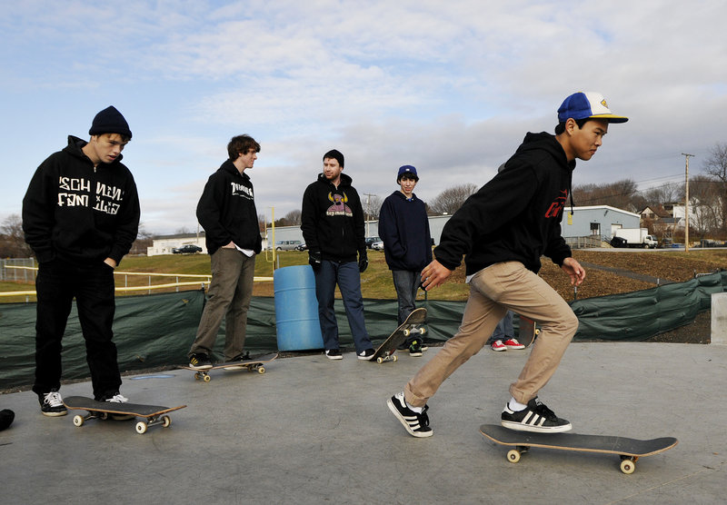 Phivann Phum 19, of Portland takes off into the skatepark as other riders look on.