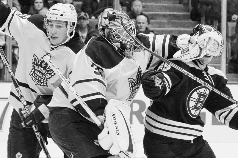 Toronto goalie Jean-Sebastien Giguere blocks Boston's Blake Wheeler as Keith Aulie battles for the puck behind Giguere. Giguere made a key stop in the shootout to give the Maple Leafs a win over the Bruins on Saturday.