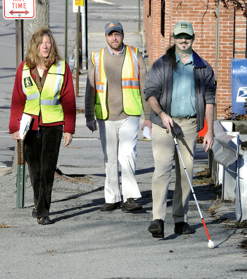 Reporter Ray Routhier, center, shadows Caitlyn Blodget as she instructs Wayne Lawson of Portland, who is visually impaired, how to get around outdoors using a cane.