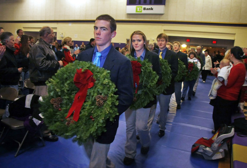 Lars Murphy and other members of the Cheverus High School swim team lead the procession of wreaths into the Cheverus gymnasium as Wreaths Across America made a stop at the school for a special ceremony Sunday.