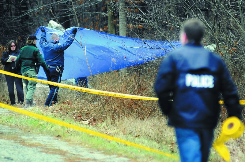 Andy Molloy/Kennebec Journal Police cover a body discovered Sunday by game wardens off Winthrop Street in Hallowell. Wardens searching with dogs located the body about noon near a granite quarry.u FEFF