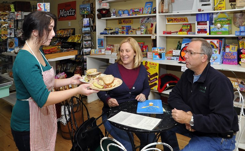 Surrounded by S. Fernald's eclectic collection of gifts, toys and Moxie memorabilia, waitress Carisa Salerno serves specially named sandwiches to regular customers Vicki and Charles Miller from Bremen.