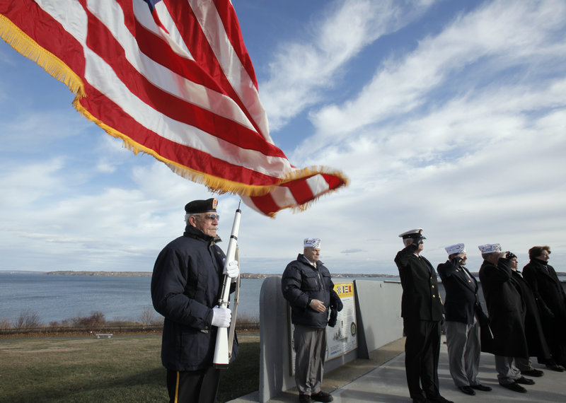 Bill Kiley, left, stands at attention at the start of a ceremony at Fort Allen Park in Portland on Tuesday, an event marking the Dec. 7, 1941 attack on Pearl Harbor. The ceremony was hosted by Amvets, Post #25 in Portland.