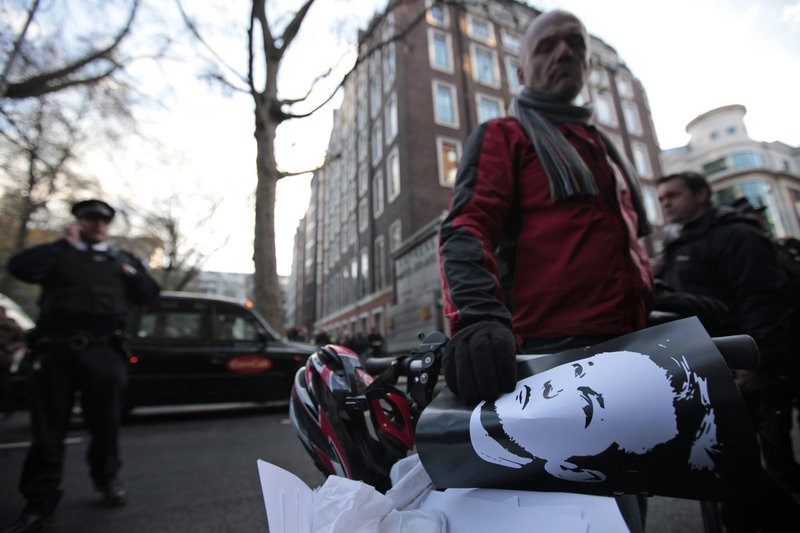 A supporter of WikiLeaks founder Julian Assange, holding a poster with Assange's image on it, gathers with others outside the City of Westminster Magistrates Court in London where Assange's case was heard on Tuesday.