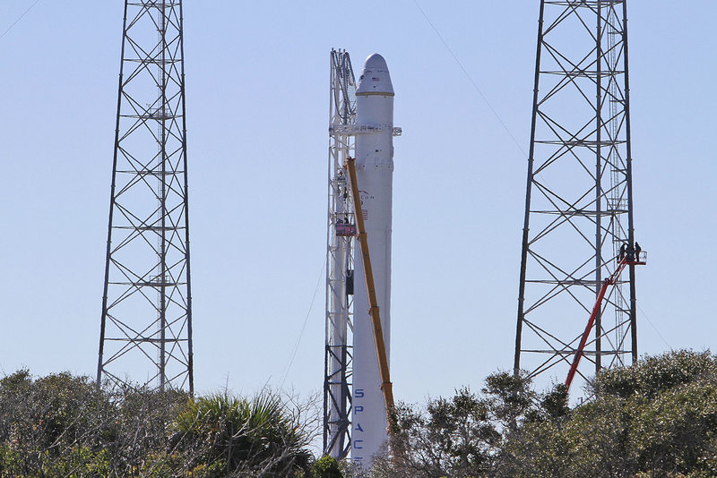 SpaceX's Falcon 9 rocket, shown Tuesday at Cape Canaveral, Fla., could blast off as early as today. If all goes as planned, the unmanned capsule it propels into orbit will circle the Earth twice, re-enter the atmosphere and splash down in the Pacific Ocean.