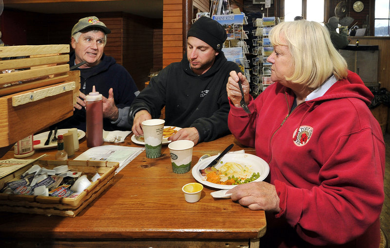 Linda Bean takes a break at her Port Clyde General Store to eat lunch with local residents Herb Beherrell, left, and Joshua Eldridge. Her conservative views influence her business strategy, with includes a deep distrust of Canada.