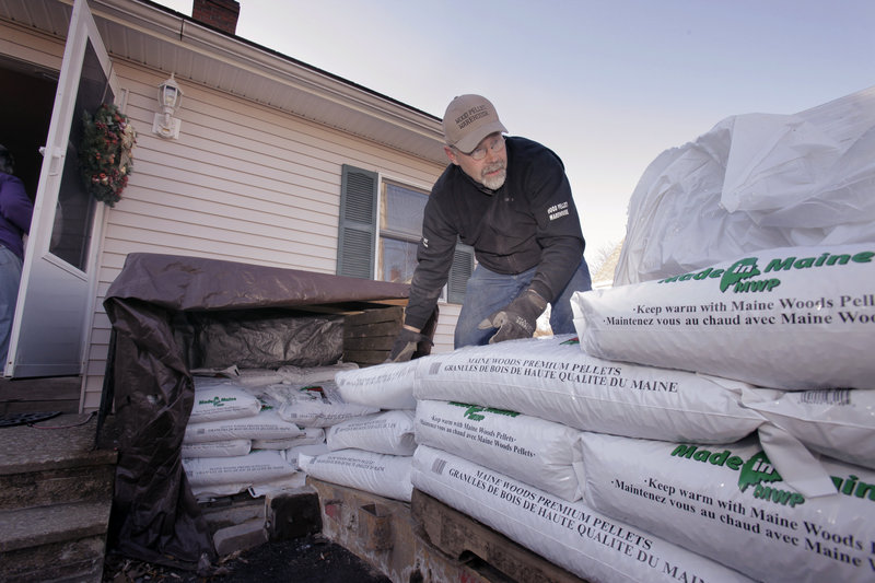 Steve Barker unloads wood pellets from his trailer Wednesday at a home in Portland. Barker and another driver are on the road daily delivering pellets from Kittery to the Bangor area.
