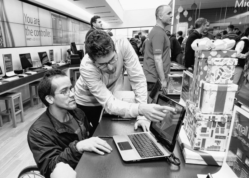Employee Matt Macy, right, shows a laptop last month to Jon McKenna at the opening of a Microsoft Store in Bellevue, Wash. McKenna bought the first laptop sold at the store.