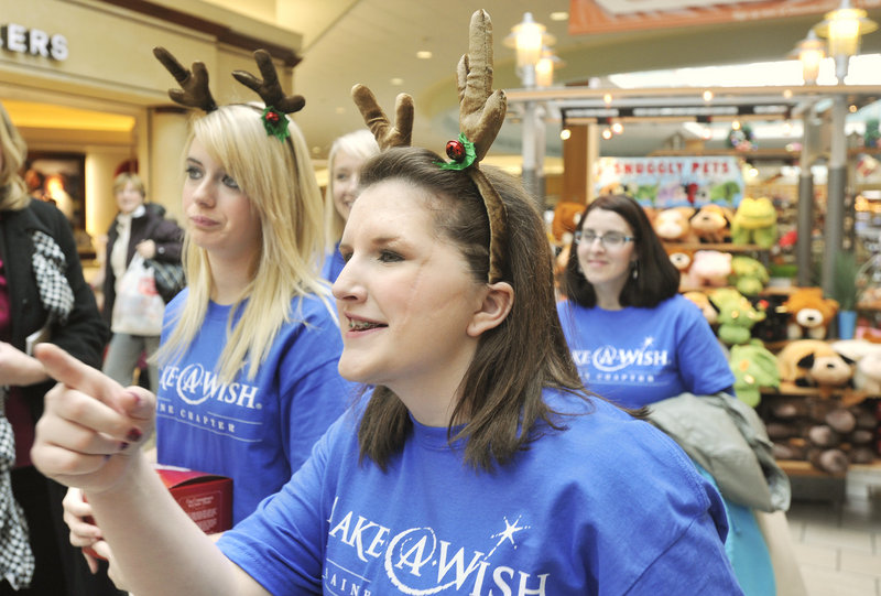 Nicole Guerrette, accompanied by her mother, sister and cousin, gets to the business at hand Friday: a shop-a-thon at the Maine Mall, courtesy of the Make-A-Wish Foundation.