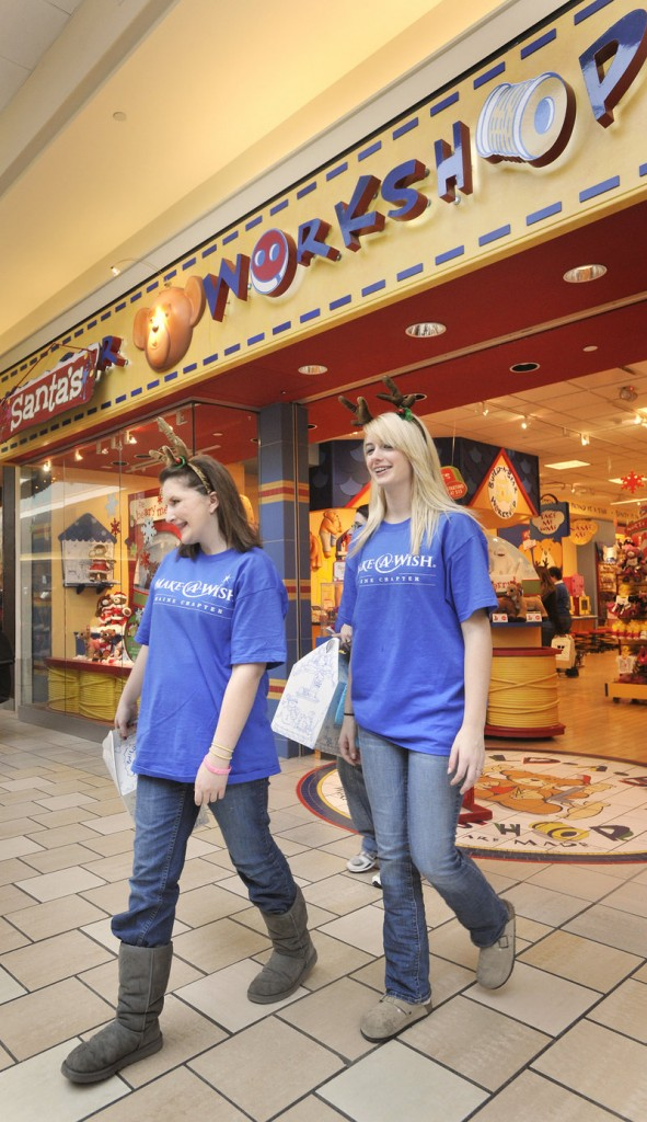 "Nicole Guerrette, left, leaves the Santa's Workshop store at the Maine Mall with her cousin, Courtney Perry, during Friday's shopping spree. ""They have done so much for me,"" Guerrette says of the Make-A-Wish Foundation. ""I want to do something for them after this is all over."""