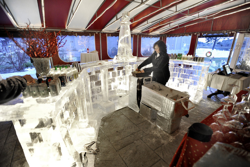 Bartender Teresa Gamache sets up her newly created ice bar at the Fire & Ice Bar benefit on Friday at The Nonantum Resort in Kennebunkport. Sculptor Ed Jarrett created the 18-foot-long bar from 16 blocks of ice. The two-night event continues from 4:30 to 9 tonight.