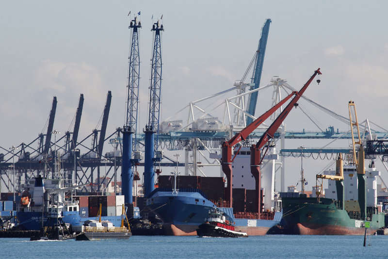 Containers are loaded onto vessels at the Port of Miami on Wednesday. The U.S. trade deficit fell to its lowest level in nine months due to a surge in exports and a drop in imports, according to international trade statistics for October.