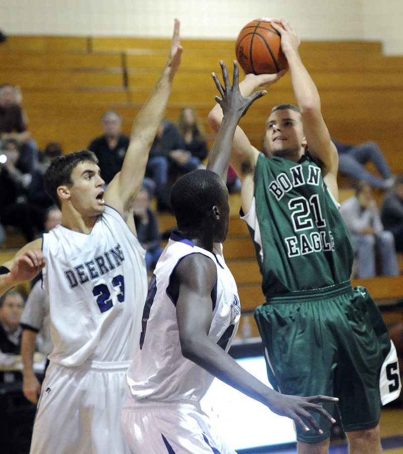 Levi Meggison of Bonny Eagle finds room to shoot Friday night over Nick Colucci, left, and Labson Abwoch of Deering. Bonny Eagle opened with a 44-41 victory.