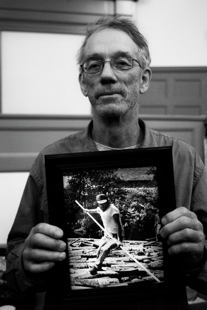 Veteran log driver Dave Calder holds a photo of himself in the early 1970s. He spoke in Bath on Dec. 8.